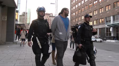 special unit : 4K UHD - Riot police walking with a protester in handcuffs. Two police officers with riot gear and uniform walk while holding the arm of protester in custody at protest.