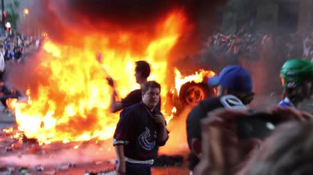 caos : Hockey fans take pictures in front of burning car at riot. Multiple people take pictures of them self in front of a car on fire in the middle of a crazy angry crowd of rioters in the city at daytime. Vídeos