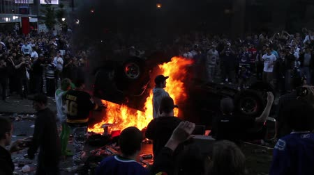 caos : Man sets car on fire in front of crazy rioters. Man lights up a car on fire with cigarette lighter in front of cheering intense rioters in chaos.