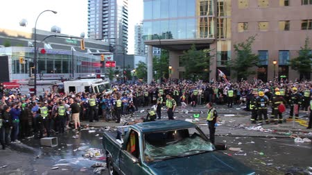 rioting : Pan left to right of massive rioting crowd - 1080p - Thousands of people rioting and throwing trash with smoking car debris and policemen and firemen.