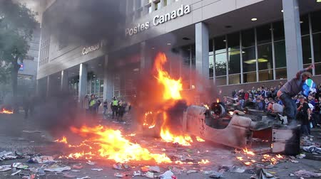 unrest : Rioter pull down pants and moons burning car. Young man steps on newspaper box and pull down his pants mooning at upside down burning car with debris.
