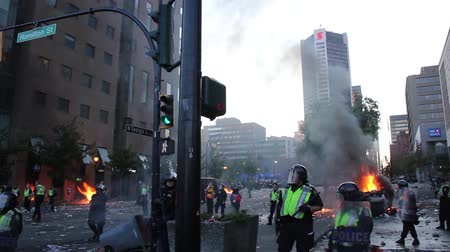 fire officer : Tear gas exploding at chaotic downtown riot. Multiple fires burn and tear gas bombs explode with riot officers with gas masks and shields and automatic heavy fire in a city core with high-rise buildings.