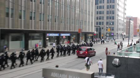 unrest : Elevated view of police line marching through city center. Long line of tactical police officers walking downtown with buildings in the background. Stock Footage
