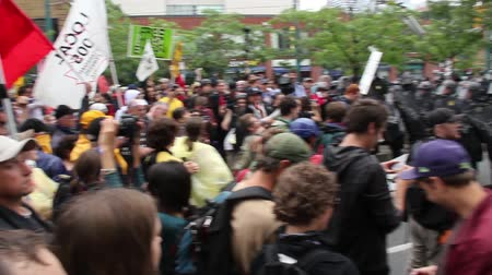 protesto : People chanting at protest with riot police in line - HD 1080p - Pan over a large crowd of protesters and demonstrators with signs and flags standing and chanting in front of police line.