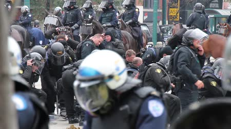 unrest : Riot police officers donning gear near horse droppings. Riot police donning equipment and gas mask with horse droppings on the ground.
