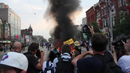 протест : Man with cowboy hat and gas mask throws political sign in fire. Man wearing old school gas mask and guitar posing and throwing a sign in a fully involved police cruiser fire.