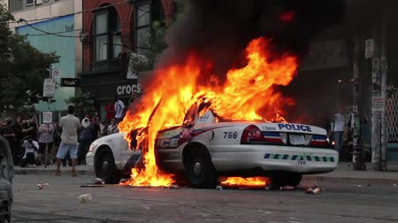 fire officer : Police car on fire with electrical explosion - HD 1080p - Police car on fire explodes at the 11 second mark with white sparks in a crowd of rioters.