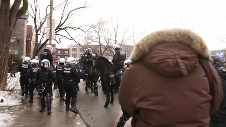 unrest : Riot police backs off while rioters shout at them. Rioters intimidate and push away police officers on horses.