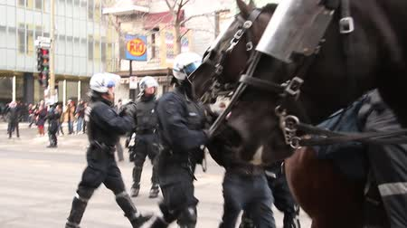 протест : Man lifted up and carried away by riot policemen. Young man being arrested and carried away by two riot officers all walking towards the camera.