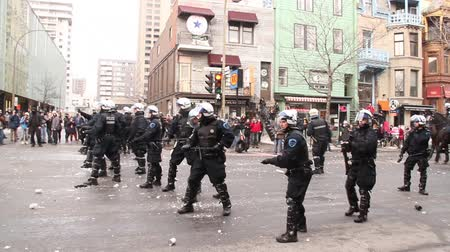 polícia : Riot officer fires rubber bullet towards cameraman. Riot police officer aims and shoots towards the camera while rioters throw glass bottles and snow balls to them. Stock Footage