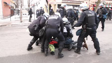 protesto : Group of tactical police officers catch and arrest rioter. A man is tackled to the ground and arrested by multiple riot officers.