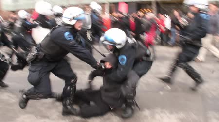 насилие : Riot officers charge group of rioters violently - HD 1080p - A riot officer hits and catch a protester violently while another protester is being carried away by officers in the background.