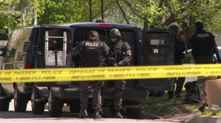 special unit : SWAT officers prepare for standoff and put on heavy gear and equipment near their truck with police line tape and sunny day.
