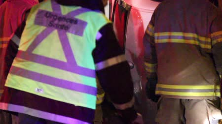 lieutenant : A fire fighter on the scene of a rollover accident is climbing into a car through the broken back window of a sedan car