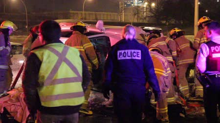 firemen : Firemen and paramedics working on extricating a man out of his car after it crashed and rolled on its side