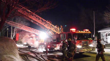fire suit : Multiple fire fighters are walking through firetrucks in direction of a house on fire with heavy flames and smoke showing Stock Footage