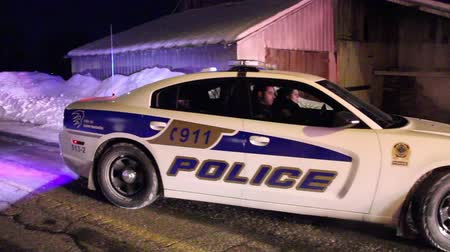 prowl : A Dodge Charger with a female officer driver is pulling away from a crime scene on a snowy road at night