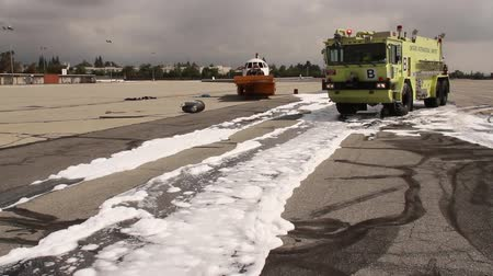letadlo : Airport crash tender with trail of foam An airport fire appliance firetruck and fire apparatus with airplane in the background and moving trail of water and white foam after firefighting