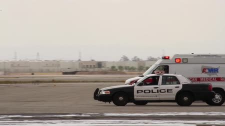 karetka : Police car driving on tarmac with plane wreck A crown victoria black and white police cruiser and ambulance stopping to talk to each other and rolling in the background with airport firetruck and airplane in the foreground
