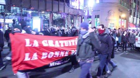 protesto : Protester giving the finger to the camera Young anarchist people wearing masks are marching and singing slogans at night with flags and one show the finger