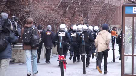 rioting : Riot officers running after people hiding A group of riot police is chasing protesters on a sidewalk while protesters are escaping into a University building Stock Footage