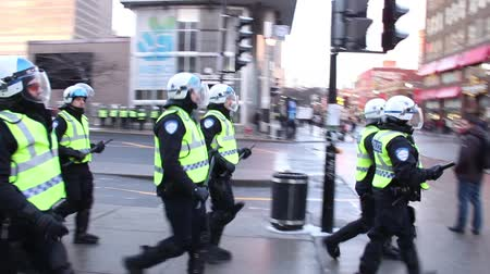 rioting : Riot police team marching and patrolling A group of riot officers is walking down the street with protective equipment and shields Stock Footage