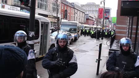 rioting : Woman arguing with riot police officer A woman is having a heated conversation with a riot officer with a mass arrest of over 30 people in the background Stock Footage