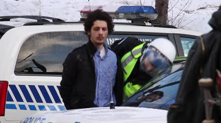 rioting : Man arrested, searched and put in cruiser Police arrest and handcuff a young man and put him in a police car Stock Footage