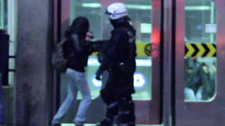 протест : Riot officers pushing girl with camera A girl filming a protest is pushed by armed police officers in front of subway station