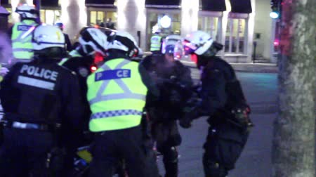 rioting : Man on bicycle arrested by riot officers A man is overwhelmed and surrounded by police officers that are handcuffing and arresting him Stock Footage