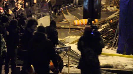rioting : Men rioting and breaking fences Two men are pulling a fence apart and one is confronting a news cameraman while his crew member is backing him up