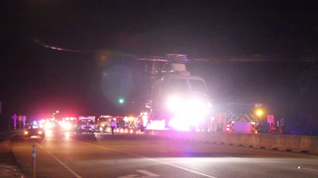 acil durum : MEDEVAC helicopter taking off from crash scene White MEDEVAC taking off at night and flying in the air at night on a highway with emergency vehicles with flashing lights in the background. Stok Video