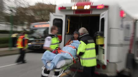 ambulância : Asian male carried in an ambulance Older looking Asian male fire victim being carried in a stretcher and pulled into a waiting ambulance by paramedics. Stock Footage