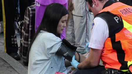 давление : Paramedic helping Asian female burn victim Young Asian woman showing black burnt marks is being attended and assessed by male paramedic and taking her blood pressure.