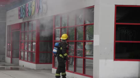 lutador : Fireman swinging pike pole and breaks windows Fire fighter breaking windows of a Toy R Us store with a fireman hook with smoke showing during the day while two others walk in front of the camera with scanner audio.