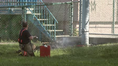 pompki : Fireman using backpack fire pump to extinguish grass fire Wideo