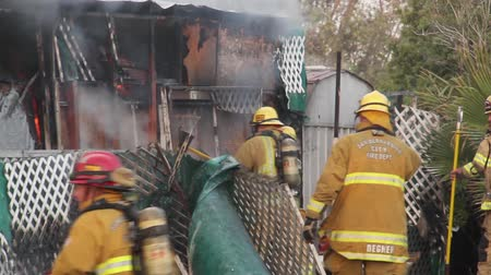 firemen : Firemen fighting fire with axe and chainsaw Fire fighters are battling a trailer park house fire at daytime with tools and equipment with cop cruiser and firetruck in the foreground