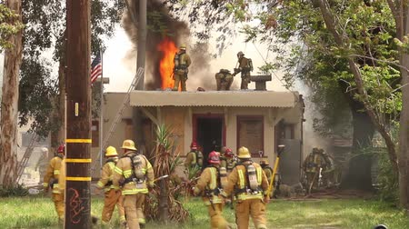 firemen : Fireman removing SCBA with flames in the background Fire fighters battle a house fire from the roof and ground with flames and smoke showing at daytime Stock Footage