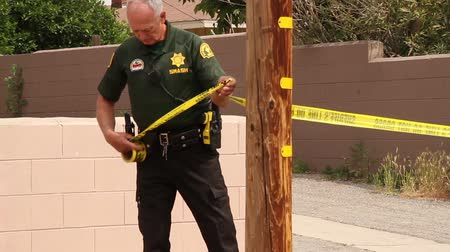 suç : Sheriff officers unrolling crime tape Sheriff and SMASH members setting up crime tape around a perimeter in green and beige uniform