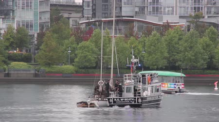 marynarka wojenna : Police boat intercepting sailboat with watertaxi in background Large marine police boat stop a sailboat with officers talking and chatting with sailboat occupant. Wideo