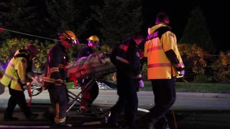 paramedic : Emergency crew carrying patient in stretcher Firemen and ambulance medics carry a male victim in a stretcher with a blanket with dead body in the background laying under a yellow tarp. Stock Footage