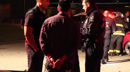 policeofficer : Driver with handcuffs at car crash scene Suspected dui driver young native male handcuffed talking with police officer at night with car wreck in the background. Stock Footage