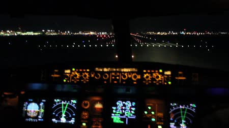 letadlo : Airplane flight deck lining up with runway at night Aircraft cockpit dashboard with multiple lights and radar turning slowly and lining up with runway lights in preparation for take off.