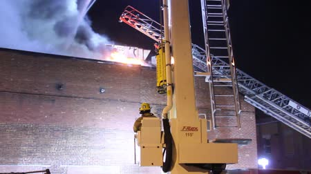 firemen : Fireman sits and controls articulating ladder truck Fireman sitting and controlling articulating platform from command seat with flames in the background Stock Footage