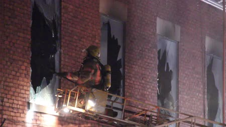 firemen : Fire fighter reaches out and breaks windows with pole Fireman at end of ladder approaching brick building and breaking windows with long pike pole tool