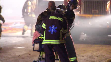 firemen : Paramedics pulling away injured fireman towards bright light Pair of ambulance staff carry a male fire fighter with oxygen mask on stretcher between hoses and firemen Stock Footage