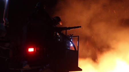fire suit : Silhouette of fireman with bright flames in background Firefighter in elevated nacelle with wind anemometer and water hose with flames in the background Stock Footage