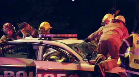 firemen : Fire fighters climbing removing windshield off police cruiser Firemen pulling on windshield and bending it down while others use jaws of life Stock Footage