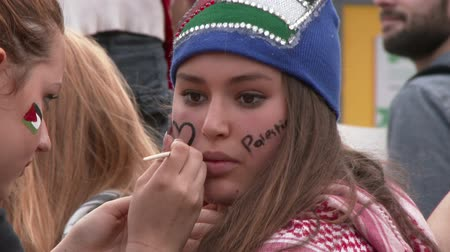 filistin : Pretty girl getting face paint in support for Palestine Female protester in support for Gaza is getting her face painted with a heart and the word Palestine Stok Video