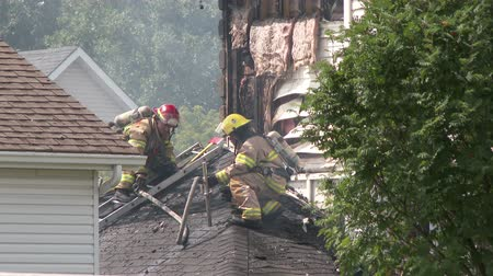 aeróbico : Fireman punches hole in roof with piercing nozzle Fire fighter using piercing nozzle to punch a hole in a roof and spray water into it on daytime fire incident Stock Footage